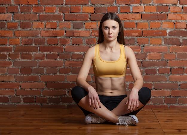 Fitness meisje, zittend op de vloer Premium Foto