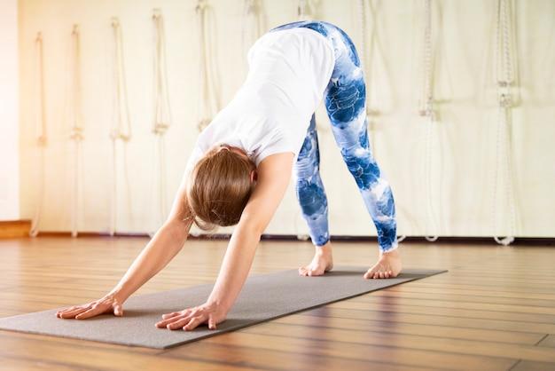Fitness, sport, opleiding en levensstijlconcept - vrouw het uitrekken zich op mat in gymnastiek Premium Foto