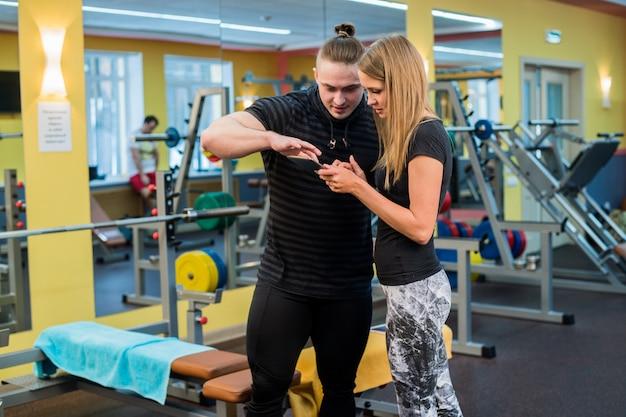 Fitness, sport, sporten, technologie en voeding concept. lachende jonge vrouw en personal trainer met smartphone in de sportschool Premium Foto