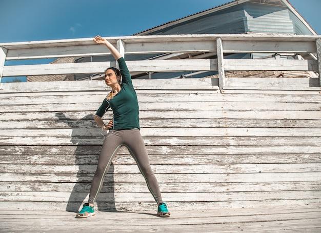 Fitness sportieve meisje in sportieve kleding doet oefeningen op een houten achtergrond, lichte achtergrond, het concept van sport Gratis Foto