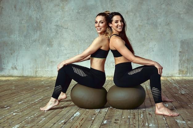 Fitness training, twee slanke mooie vrouwen trainen in de fitnessruimte. Premium Foto