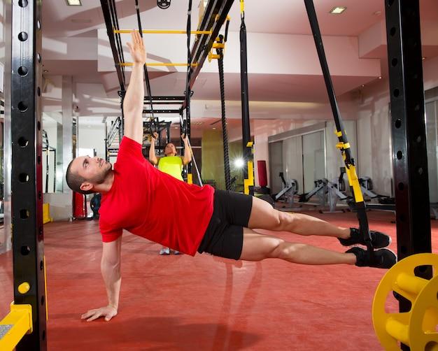 Fitness trx-trainingsoefeningen bij gym vrouw en man Premium Foto