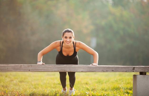 Fitness. van sport, recreatie en motivatie. atletische vrouw die zich in plankpositie in openlucht bij zonsondergang bevinden Premium Foto