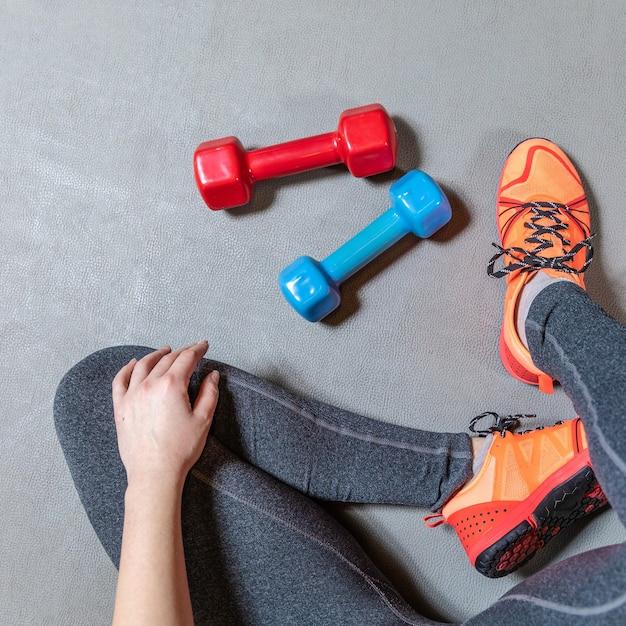 Fitness vrouw benen met kleurrijke halters bovenaanzicht Premium Foto
