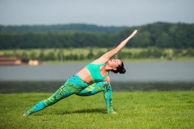 Fitness vrouw doet yoga oefening en ontspannen met sportkleding in groen park in de zomer Gratis Foto