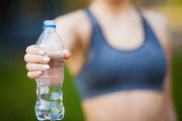 Fitness. vrouw hand met drinkwater fles Premium Foto