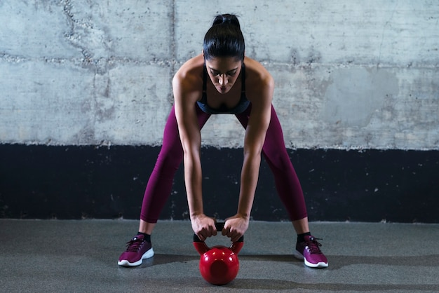 Fitness vrouw in sportkleding trainen met het gewicht van de waterkoker bell in de sportschool Gratis Foto