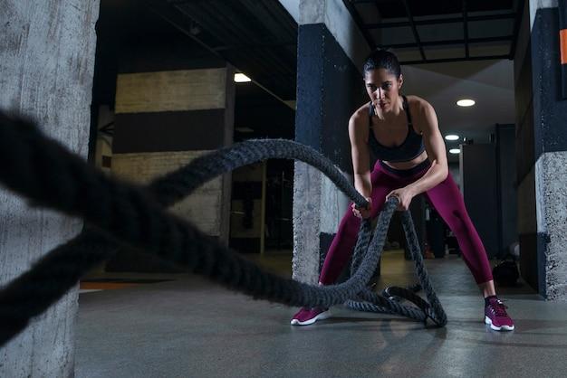 Fitness vrouw uit te werken met touwen van de strijd in de sportschool Gratis Foto