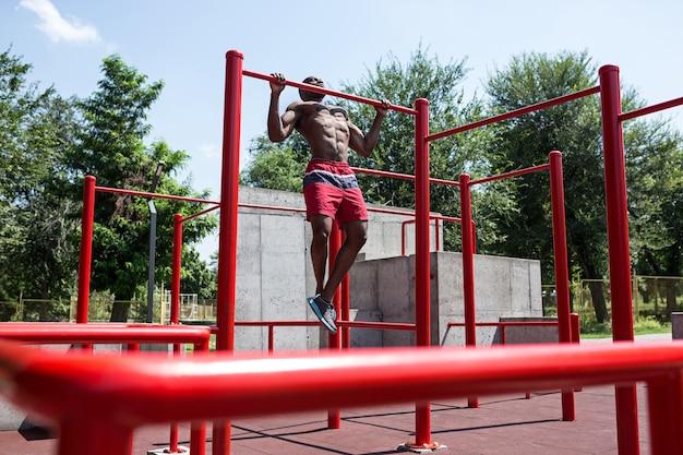 Fitte atleet die oefeningen doet in het stadion. afro of afro-amerikaanse man buiten in de stad Gratis Foto
