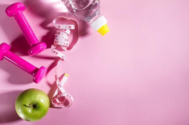 Flat lay sport concept gezond leven apparatuur op heldere roze achtergrond. close-up met kopie ruimte. Gratis Foto