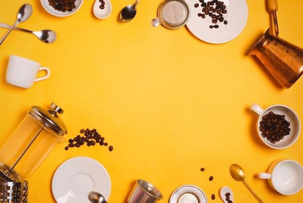 Flatlay met verschillende koffiezetaccessoires, apparatuur en keukengerei: cezve, franse pers, vietnamees phin-filter enz. op geel Premium Foto