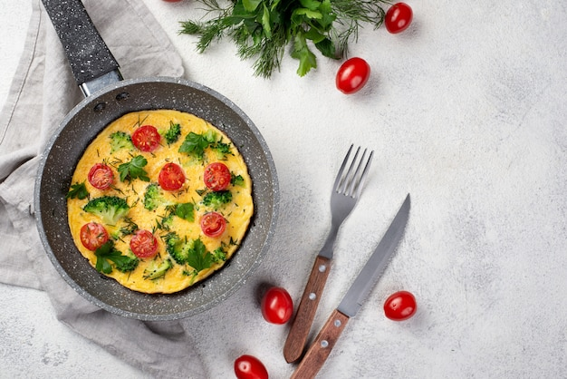 Flay leg ontbijtomelet in pan met tomaten en bestek Gratis Foto