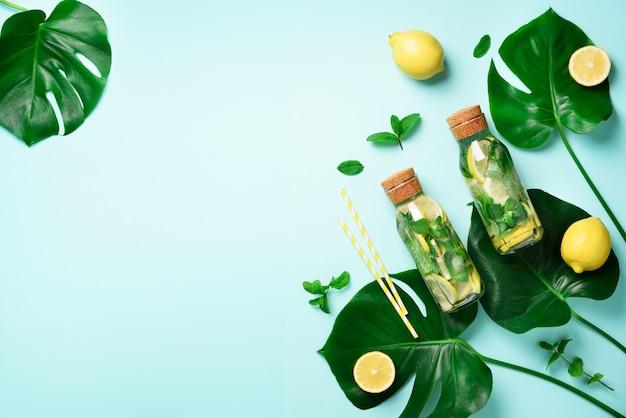 Fles detoxwater met munt, citroen en tropische monsterabladeren op blauwe achtergrond. Premium Foto
