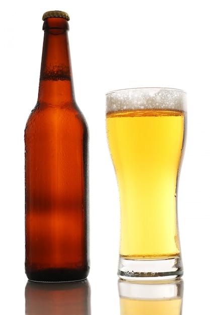 Fles en een glas bier met schuim op witte achtergrond wordt geïsoleerd die Premium Foto