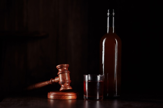 Fles en glas met whisky en rechter hamer, alcohol en misdaden concept. Premium Foto