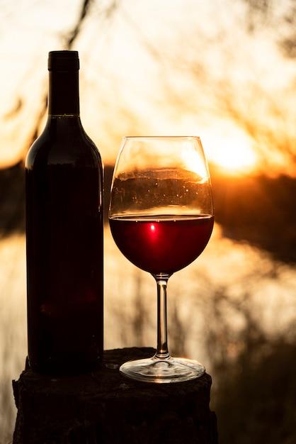 Fles en wijnglas met stralende zon op de rug Gratis Foto