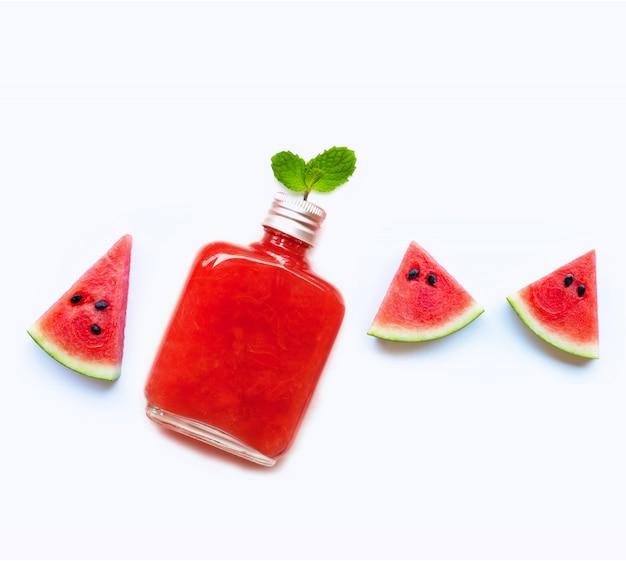 Fles gezond die watermeloensap met plak en muntbladeren op wit worden geïsoleerd Premium Foto