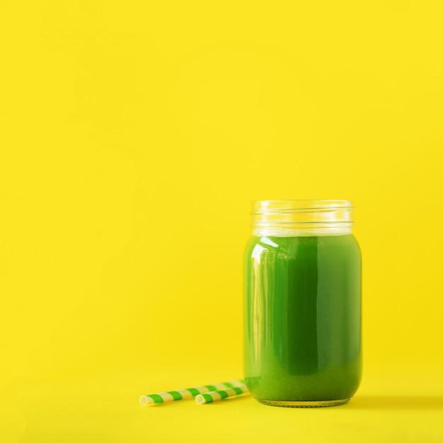 Fles groene selderie smoothie op gele achtergrond Premium Foto