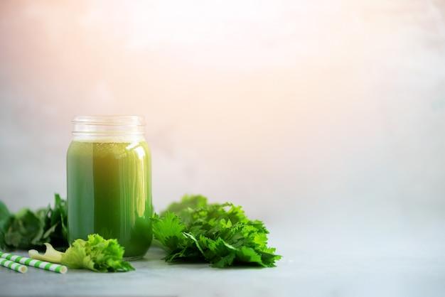 Fles groene selderiesmoothie op grijze concrete achtergrond Premium Foto