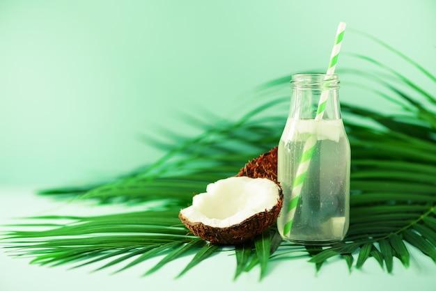 Fles kokoswater en vers rijp fruit. vegetarisch, veganistisch, detoxdrankje. kokosnotensap met stro op palmbladen Premium Foto