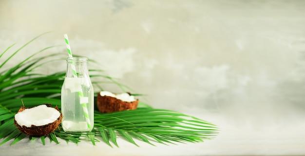 Fles kokoswater en vers rijp fruit. zomer eten concept. vegetarisch, veganistisch, detoxdrankje. kokosnotensap met stro op palmbladen Premium Foto