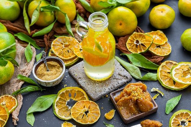 Fles mandarijnwater op een tafel omringd door droge citrusvruchten mandarijn poeder en jam Gratis Foto