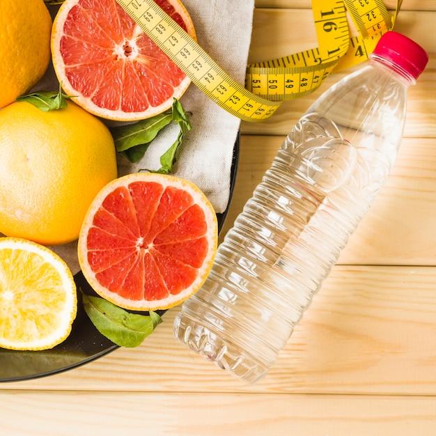 Fles; meetlint en citrusvruchten op plaat Gratis Foto