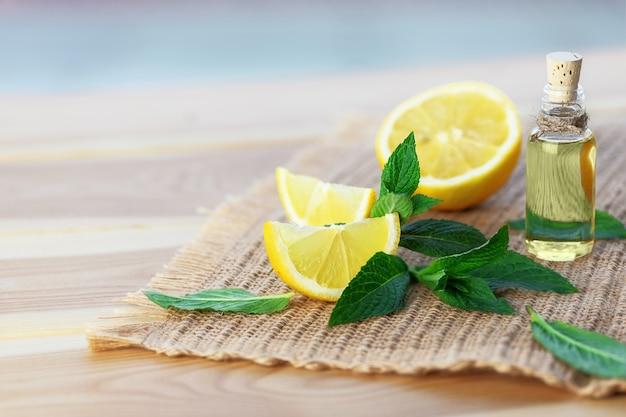 Fles met muntolie, citroen en verse groene muntblaadjes op houten achtergrond. selectieve aandacht. Premium Foto