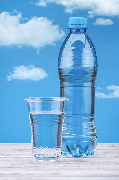 Fles met water op witte tafel en blauwe achtergrond met wolken. zoet water in plastic beker Premium Foto