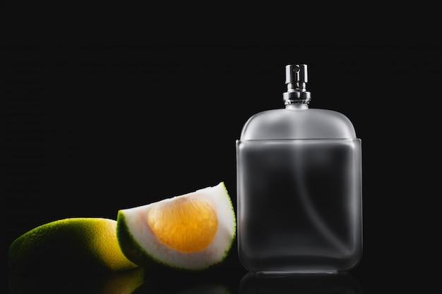 Fles moderne mannelijke parfum en citrus plakjes op donkere achtergrond Premium Foto