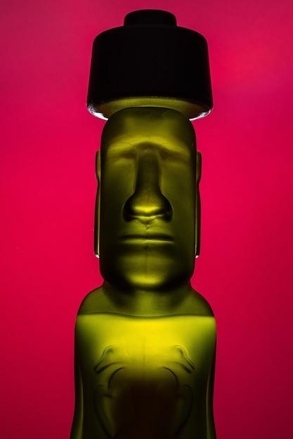 Fles of sculptuur van groene en gele kleur humanoïde moai geïsoleerd op rode achtergrond, rapanui Premium Foto
