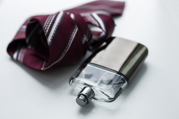Fles parfum voor mannen met stropdas op een witte achtergrond. Premium Foto