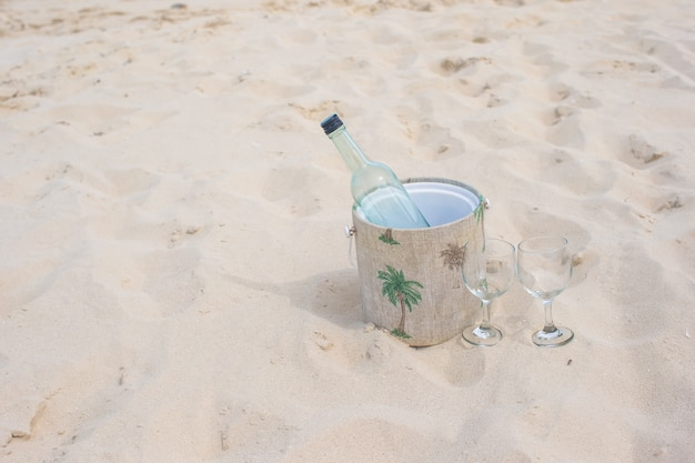 Fles wijn en twee glazen op zandstrand Premium Foto
