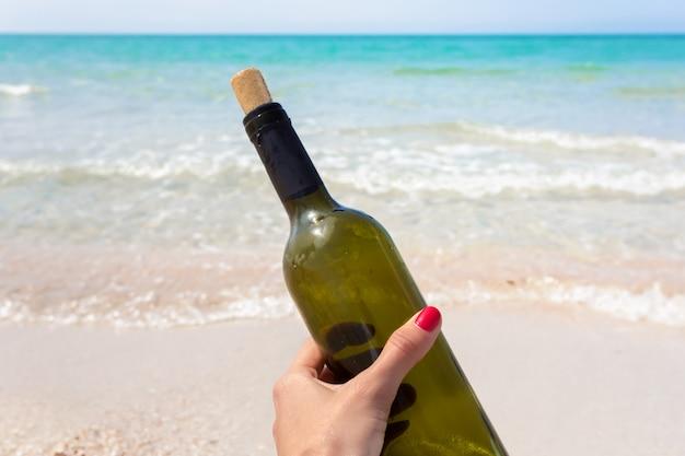Fles wijn in zand op het strand Premium Foto
