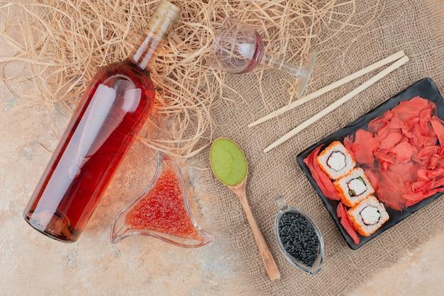 Fles wijn met wijnglas en sushi op jute Gratis Foto