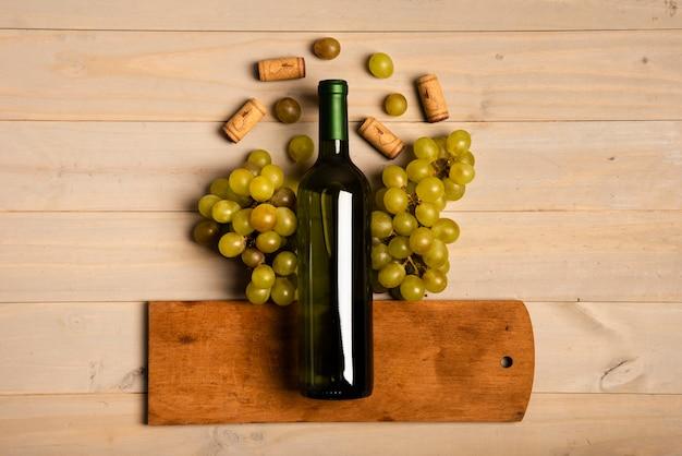 Fles wijn op snijplank dichtbij druiven wordt gelegd die Gratis Foto