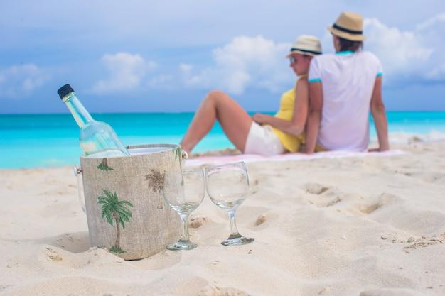 Fles witte wijn en twee glazen achtergrond gelukkig paar op zandstrand Premium Foto