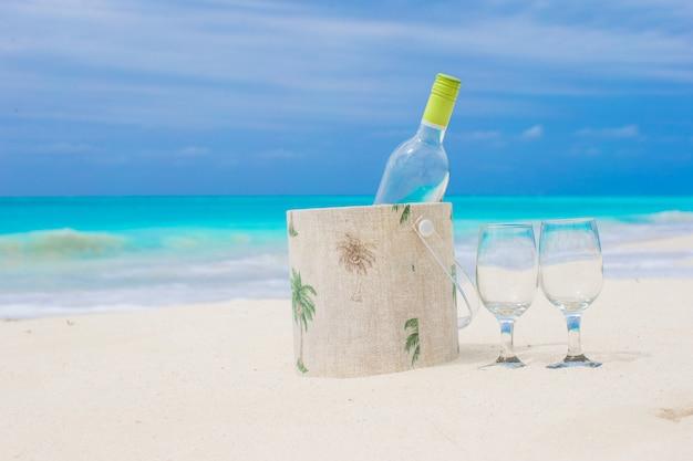 Fles witte wijn en twee glazen op het exotische zandstrand Premium Foto