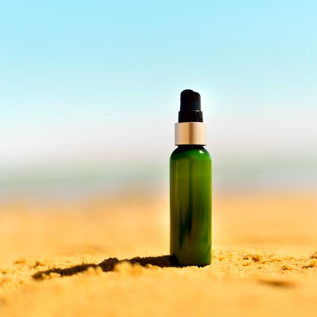Fles zonnescherm in zand tegen overzeese achtergrond. vakantie en reizen behang. huidverzorging concept. Premium Foto