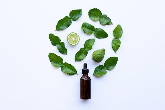 Flesje etherische olie en verse kaffir limoen of bergamot fruit met bladeren Premium Foto