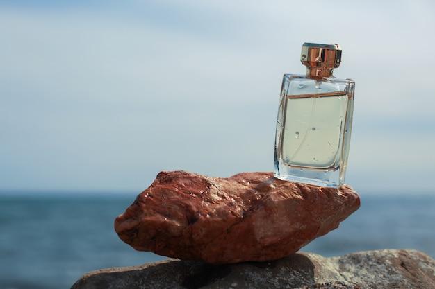 Flesje vrouwenparfum op de achtergrond van de zee Premium Foto