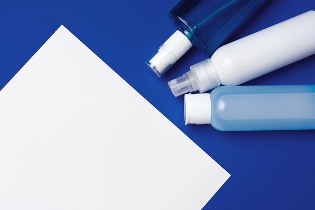 Flessen met antibacterieel handdesinfecterend middel op blauw met exemplaarruimte Premium Foto