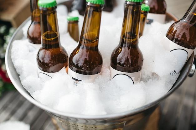 Flessen met bier koelen in een emmer met ijs Gratis Foto