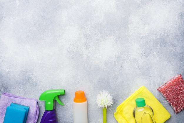 Flessen met detergentia, borstels en sponsen op concrete achtergrond. Premium Foto