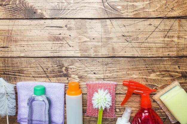 Flessen met detergentia, borstels en sponsen op houten achtergrond. Premium Foto