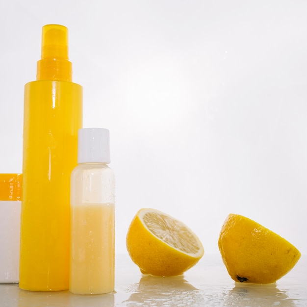 Flessen met huidverzorgingsproducten in de buurt van citroen Gratis Foto