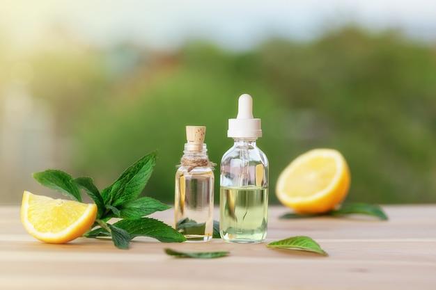 Flessen met muntolie, citroen en verse groene muntblaadjes op houten tafel. intreepupil achtergrond. Premium Foto