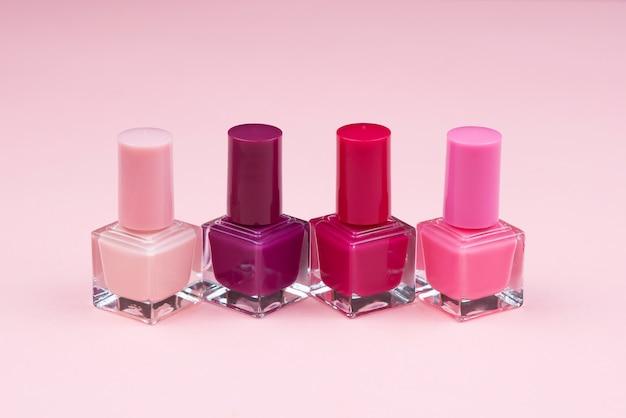 Flessen met nagellak over roze muur Premium Foto