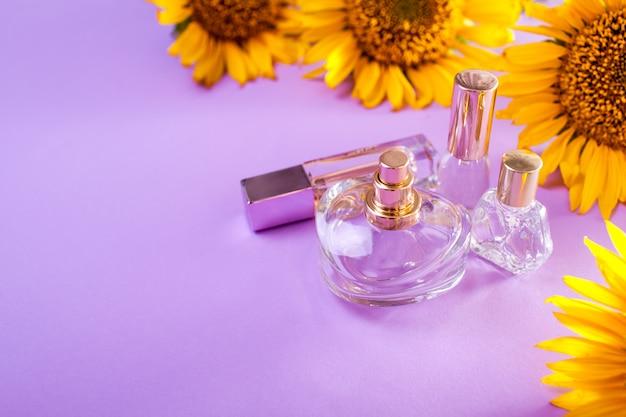 Flessen parfum met zonnebloemen op paars. biologische cosmetica Premium Foto