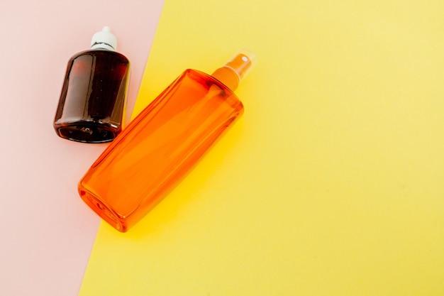 Flessen sunblock op heldere vierkante gele en roze achtergrond. het concept van het resort op zee, zomertijd. bovenaanzicht, plat lag, minimalisme, kopie ruimte Premium Foto